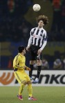 Fabricio Coloccini makes defending look beautiful while towering over Metalist's Cristian Villagra.