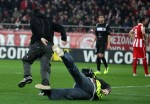 An Olympiakos security official falls on his arse while trying to catch a nifty pitch invader.