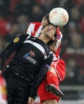 Olympiakos' Jose Holebas and Levante's Pedro Rios do battle in the air.
