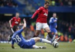 Cesar Azpilicueta attempts to poke the ball away from Javier Hernandez