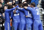 The Chelsea players smother goalscorer Demba Ba