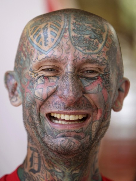 British soccer fan with tattoed face smiles as he parties in the centre of Donetsk