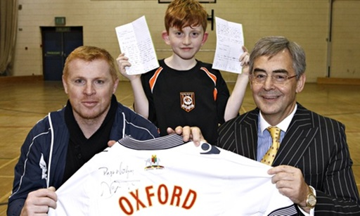 Thomas Fielding holds his job letter as Bolton Wanderers manager Neil Lennon presents a signed shirt