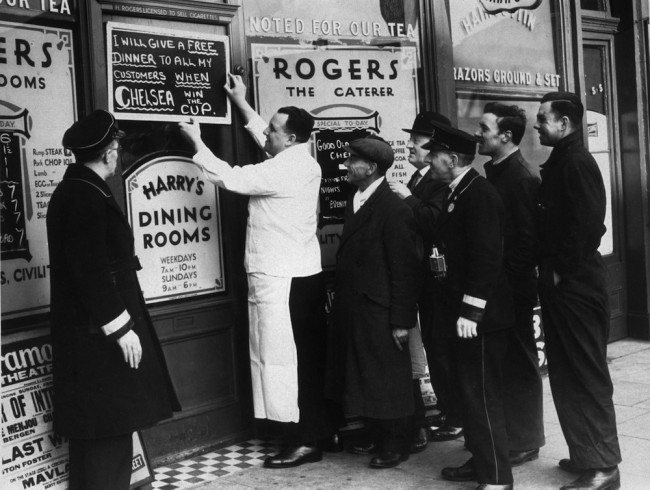 circa 1939:  Mr Roger, the proprietor of a restaurant on the Chalk Farm Road, London, putting up a notice announcing that he will give free meals to all his customers if Chelsea win the FA Cup.  (Photo by Fox Photos/Getty Images)