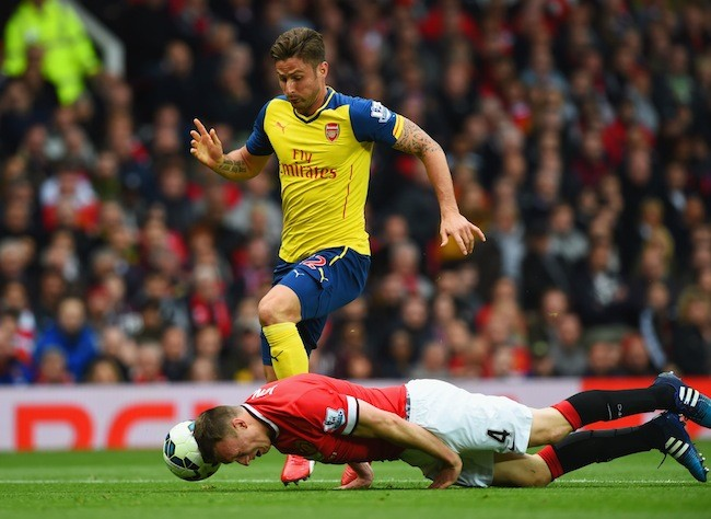 MANCHESTER, ENGLAND - MAY 17:  Phil Jones of Manchester United heads the ball clear of Olivier Giroud of Arsenal during the Barclays Premier League match between Manchester United and Arsenal at Old Trafford on May 17, 2015 in Manchester, England.  (Photo by Shaun Botterill/Getty Images)