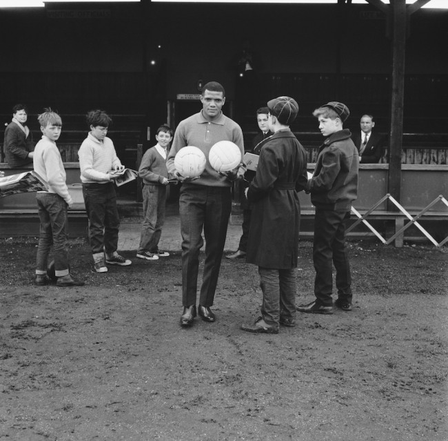 South African footballer Albert Johanneson (1940 - 1995) of Leeds United, with fans at the Hendon Football Club ground, London, during a team training session before the FA Cup final against Liverpool, 28th April 1965. Johanneson is suffering from a leg injury and is acting as a ball carrier at the session. (Photo by Keystone/Hulton Archive/Getty Images)