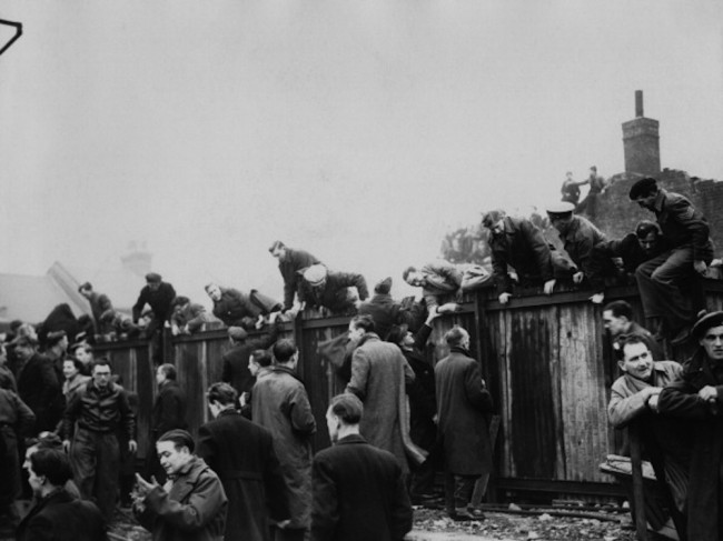Football fans climbing over a fence at Upton Park football ground to watch the cup tie between West Ham and Arsenal, London, 5th January 1946. (Photo by Central Press/Picture Post/Hulton Archive/Getty Images)