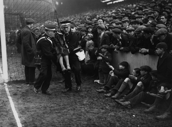 4th March 1933:  An injured spectator is removed from the crowd during a sixth round FA Cup clash between West Ham United and Birmingham City at Upton Park.  (Photo by Davis/Topical Press Agency/Getty Images)