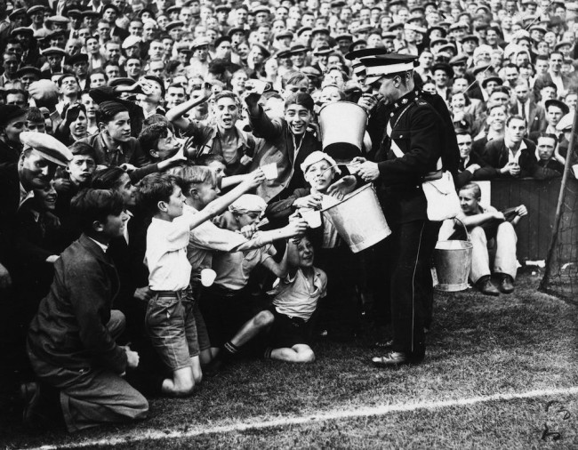 29th August 1936:  St John's Ambulancemen handing out oatmeal drinks in the heat at the football match between West Ham United and Tottenham Hotspur at Upton Park.  (Photo by E. Dean/Topical Press Agency/Getty Images)