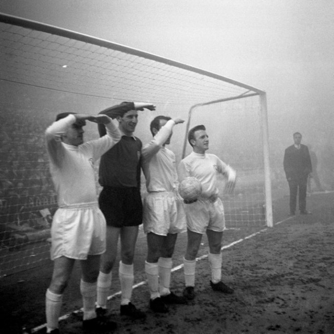 Tottenham Hotspur players, left to right, Dave MacKay, goalkeeper Bill Brown, Jimmy Greaves and Terry Dyson peer out into the fog in search of Manchester United players. The match was postponed because of very poor visibility.